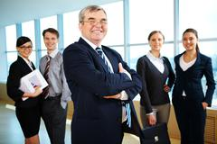 Image of senior leader smiling at camera with young business partners behind Stock Photos