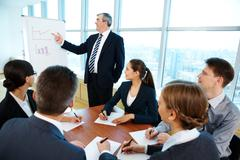 Smart and confident boss pointing at whiteboard while making presentation Stock Photos