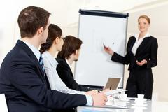 Photo of serious business people listening to female manager pointing at whitebo Stock Photos