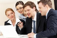 portrait of friendly workteam looking at monitor of laptop while confident busin - stock photo