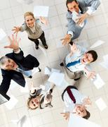Above view of several successful partners throwing papers in joy Stock Photos