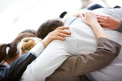Circle of business people embracing each other with their heads bowed while conc Stock Photos