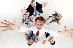 above view of happy chief being thrown by several partners upwards - stock photo