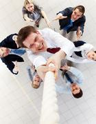 Above view of happy employer ascending up the rope with several employees beneat Stock Photos