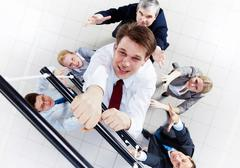 Above view of businessman ascending the ladder with his crew beneath Stock Photos