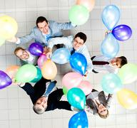 Above view of several successful partners with colorful balloons looking at came Stock Photos