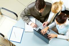 above view of several business partners interacting at meeting - stock photo
