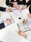 above view of friendly workteam working with documents at business meeting - stock photo