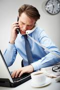 portrait of confident businessman calling by two phones and typing simultaneousl - stock photo