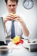 Portrait of disgusted businessman eating hamburger during lunch break Stock Photos