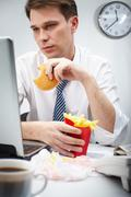 Portrait of serious businessman looking at laptop screen while eating hamburger Stock Photos