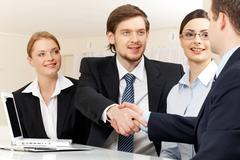 photo of successful business partners handshaking after striking deal with prett - stock photo