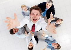 above view of happy employer looking at camera while being thrown by several par - stock photo