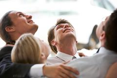 Circle of business people embracing each other while looking upwards Stock Photos