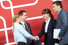 Image of businesswomen handshaking with two businessmen near by Stock Photos