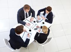Image of several employees working individually at meeting Stock Photos