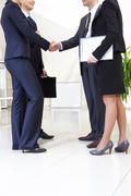 Image of business people handshaking after signing agreement Stock Photos