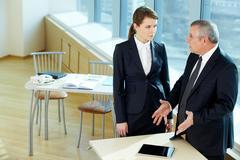 Boss explaining something to secretary in office Stock Photos