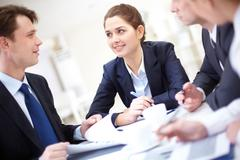 Image of pretty employee looking at business partner while discussing business p Stock Photos