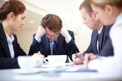 Image of frustrated businessman touching his head while his colleagues looking a Stock Photos