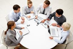 Stock Photo of image of company of successful partners discussing business plan at meeting