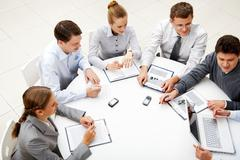 image of company of successful partners looking at their colleague at meeting - stock photo