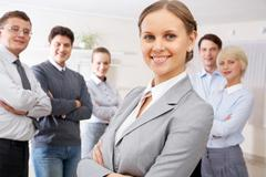 Portrait of confident business people looking at camera with pretty woman in fro Stock Photos