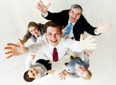 above view of happy employer looking at camera with several partners around him - stock photo