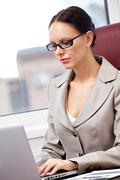 Portrait of a successful businesswoman typing in office Stock Photos