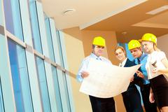Portrait of team of workers holding a project and discussing it Stock Photos