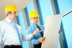 portrait of two partners holding a project and discussing it - stock photo