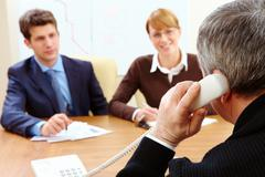 Stock Photo of rear view of bank employee calling on the phone opposite two visitors