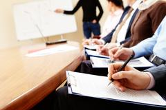 Close-up of businesspeople hands holding pens and papers near table at business Stock Photos
