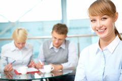 female leader looking at camera with team of partners working behind - stock photo
