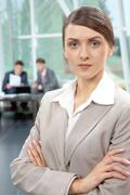 portrait of a confident businesswoman looking at camera against her colleagues - stock photo