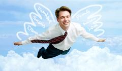 conceptual image of smiling businessman with wings flying in the clouds - stock photo