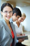 portrait of happy businesswoman smiling at camera on background of working peopl - stock photo