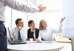 image of businesspeople pointing at board during presentation - stock photo