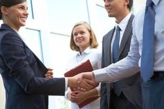 Image of business partners handshake after signing new contract Stock Photos