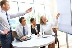 image of business partners pointing at board during presentation in office - stock photo