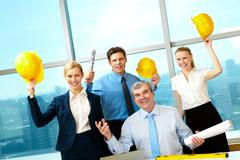 portrait of four happy workers holding papers and helmets with joyful expression - stock photo