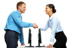 Stock Photo of two businesspeople shaking hands standing at two identical tables with computers