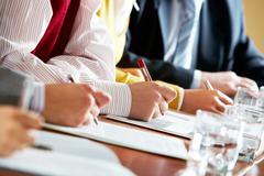 Lähikuva ihmisen kädet yrityksen asiakirjoja aikana konferenssi Kuvituskuvat