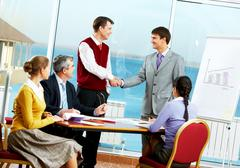 image of two partners handshaking while their colleagues looking at them - stock photo