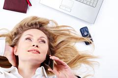 close-up of a young businesswoman lying and chattering on the phone - stock photo