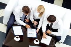 Image of company of successful partners discussing business plan at meeting Stock Photos