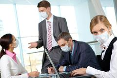 Serious businesswoman in mask working in the office Stock Photos