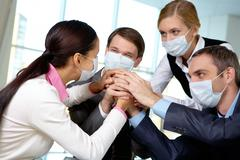 portrait of business team in protective masks making pile of hands - stock photo