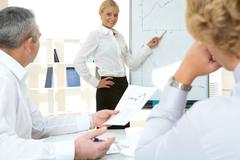 Photo of successful employee standing by whiteboard while her colleagues listeni Stock Photos