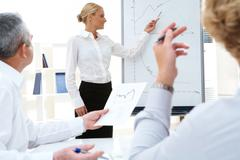photo of successful manager standing by whiteboard while her colleagues listenin - stock photo